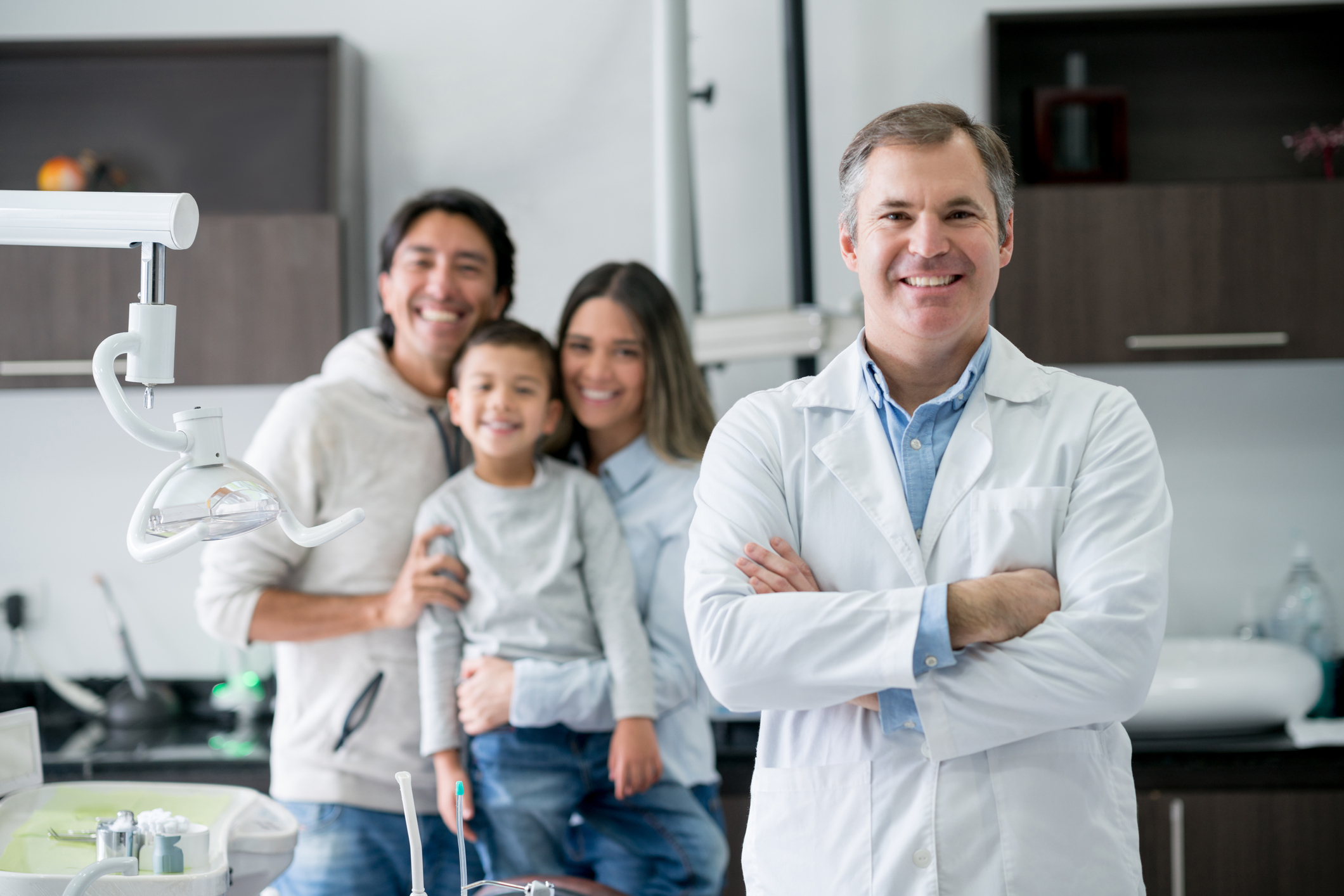 Dentist at the office looking very happy with a family at the background